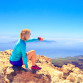 Young woman looking at natural beautiful inspirational landscape with islands and ocean, hiking trekking and recreation motivation and inspiration in sunny mountains over blue sky and ocean sea, Canary Islands.